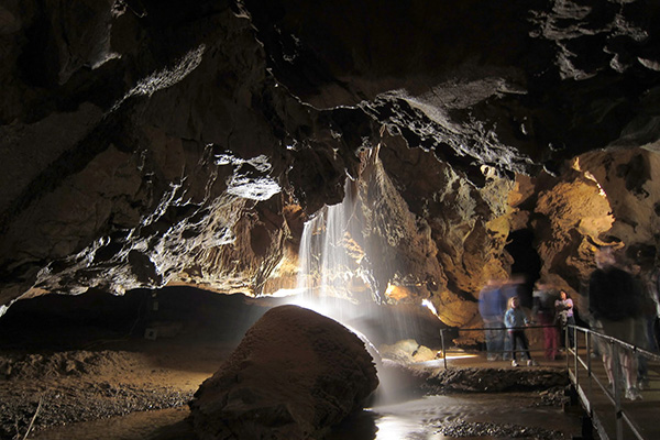 Visitors walking through Tuckaleechee Caverns and looking at a waterfall in Townsend, TN.