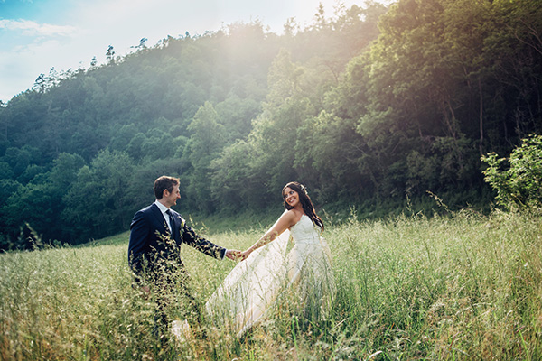 Picture of a happy bride holding her new husbands hand in a field of high grass